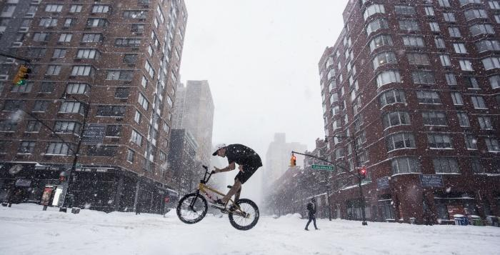 A daring biker does a barspin in the winter storm. (Jesse Carlucci/ The Observer)