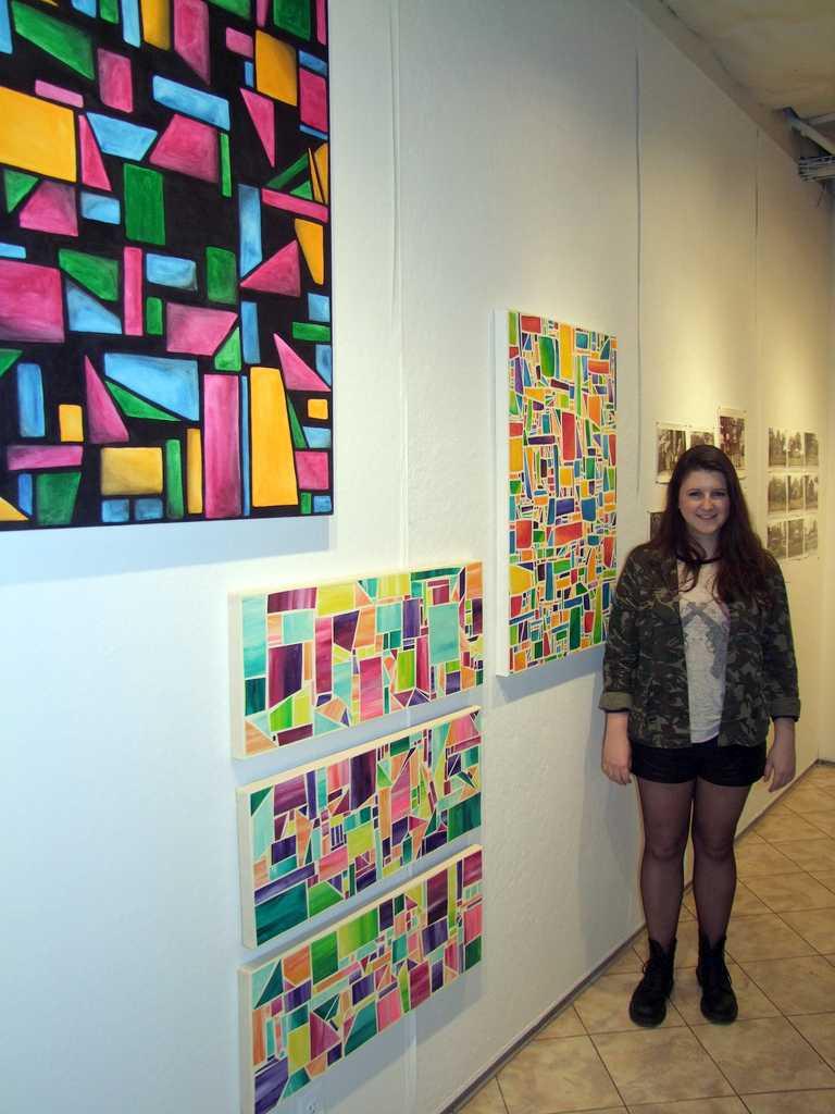 Elle Radan, FCLC'13, beside her paintings in the senior art exhibit. (Ludovica Martella/ The Observer)