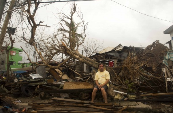 A resident sits on debris in typhoon-hit Leyte Province, Nov. 12, 2013. (Lui Siu Wai/Zuma Press via MCT)