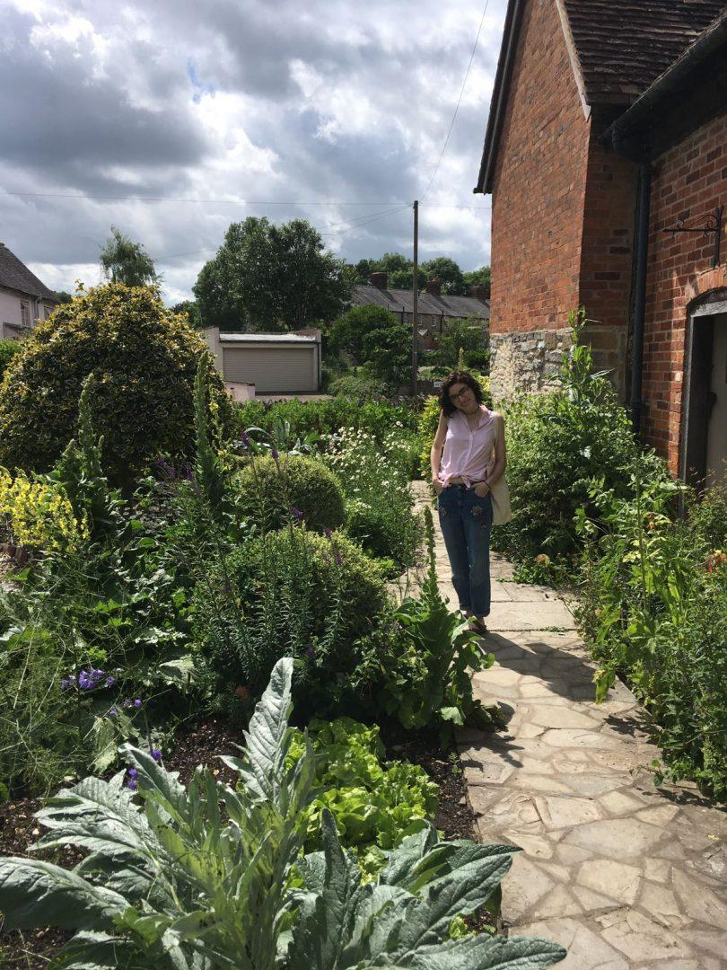 Fellow travel writing student Nadine Santoro posing next to one of the many gardens at Mary Arden's farm. (CALLAN McCARTHY/ THE OBSERVER)
